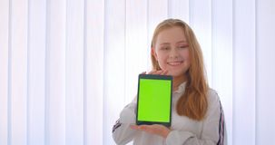 Retrato do close up da menina caucasiano bonito nova que usa uma tabuleta e mostrando a tela verde do croma à câmera que está den video estoque