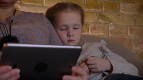Retrato do close-up da menina caucasiano pequena caucasiano com tranças que olha na tabuleta com grande interesse na casa confort video estoque