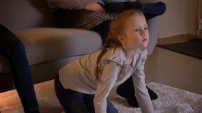 Retrato do close-up da menina caucasiano pequena com tranças que olha o filme atentamente e que aponta o dedo nele com ela filme