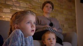 Retrato do close-up da menina caucasiano pequena com tranças que olha o filme atentamente com suas mãe e irmã sobre vídeos de arquivo