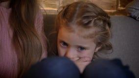 Retrato do close-up da menina caucasiano pequena que senta-se no sofá e que come um biscoito no fundo de casa acolhedor filme