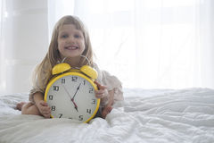Retrato do close-up da menina com o despertador enorme em suas mãos Fotografia de Stock