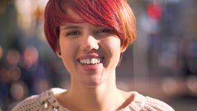 Retrato do close-up da menina cor-de-rosa-de cabelo caucasiano nova que sorri humildemente na câmera no fundo borrado da rua filme