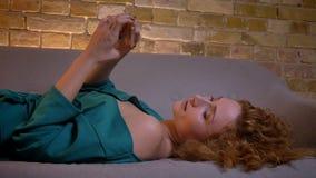 Retrato do close-up da menina encaracolado-de cabelo do gengibre que encontra-se no sofá e que olha no smartphone no fundo de cas filme