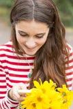 Retrato do close up da menina feliz de sorriso com as flores que olham a confusão fotografia de stock royalty free