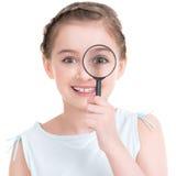 Retrato do close-up da menina que olha com de uma ampliação Fotos de Stock Royalty Free
