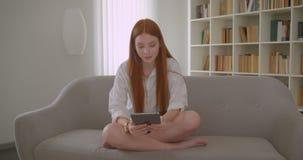 Retrato do close up da mensagem fêmea do ruivo bonito novo na tabuleta que senta-se no sofá em um apartamento acolhedor vídeos de arquivo