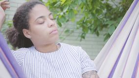 Retrato do close-up da mulher afro-americano de sorriso nova que senta-se na rede, relaxando no jardim, texting sobre vídeos de arquivo