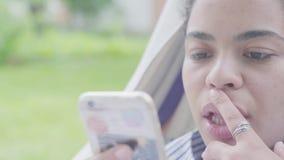 Retrato do close-up da mulher afro-americano feliz que encontra-se na rede, relaxando no jardim, texting em seu telefone celular vídeos de arquivo
