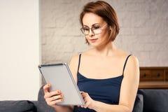 Retrato do close up da mulher alegre atrativa que descansa com tabuleta em casa Imagem de Stock Royalty Free