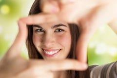 Mulher bonita nova que faz o quadro com suas mãos imagem de stock royalty free
