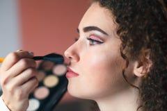 Retrato do close up da mulher bonita que obtém a composição profissional com escova Beleza e conceito da composição foto de stock royalty free