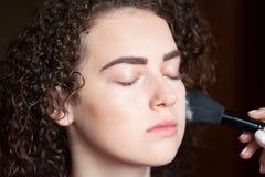 Retrato do close up da mulher bonita que obtém a composição profissional com escova Beleza e conceito da composição imagens de stock