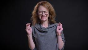Retrato do close up da mulher caucasiano de meia idade esperançosa que tem seus dedos cruzados e rezar vídeos de arquivo