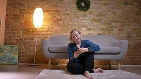 Retrato do close up da mulher caucasiano do eldery que usa o telefone ao sentar-se no assoalho em um apartamento acolhedor filme