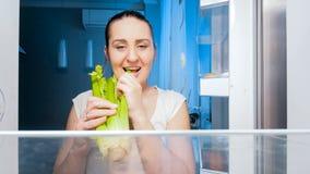 Retrato do close up da mulher com fome sonolento que come o aipo do refrigerador Imagens de Stock Royalty Free