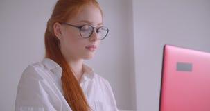 Retrato do close up da mulher de negócios caucasiano bonita nova do ruivo nos vidros usando o portátil que olha o sorriso da câme video estoque