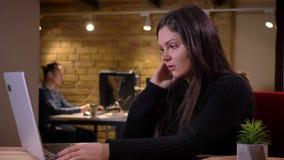Retrato do close up da mulher de negócios fêmea caucasiano moreno adulta que usa o portátil e obtendo a virada devido ao erro vídeos de arquivo