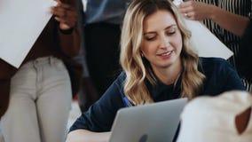 Retrato do close-up da mulher de negócios loura de sorriso nova do chefe ocupada no trabalho com os colegas na reunião moderna do filme