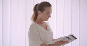 Retrato do close up da mulher de negócios moreno caucasiano idosa que lê uma posição do livro em um apartamento branco dentro video estoque