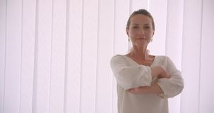 Retrato do close up da mulher de negócios moreno caucasiano idosa que olha a câmera que tem seus braços cruzados sobre a caixa video estoque