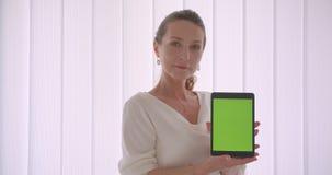 Retrato do close up da mulher de negócios moreno caucasiano idosa que usa o tabletand que mostra a croma verde a tela chave a vídeos de arquivo