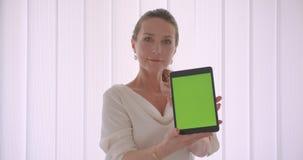Retrato do close up da mulher de negócios moreno caucasiano idosa que usa o tabletand que mostra a tela verde à posição da câmera vídeos de arquivo