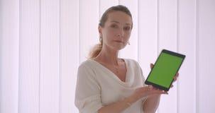Retrato do close up da mulher de negócios moreno caucasiano idosa que usa o tabletand que mostra a tela verde do croma à câmera filme