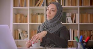 Retrato do close up da mulher de negócios muçulmana atrativa nova no hijab usando o portátil que é café pensativo e bebendo dentr vídeos de arquivo
