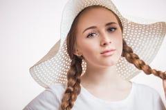 Retrato do close-up da mulher encantador nova no chapéu bege e no t-shirt que olham a câmera no branco fotografia de stock