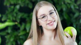 Retrato do close-up da mulher europeia de sorriso bonita que come a maçã orgânica fresca que olha a câmera filme