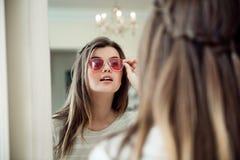 Retrato do close-up da mulher europeia moderna atrativa na loja do ótico que está o espelho próximo e que tenta em à moda imagens de stock