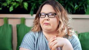Retrato do close-up da mulher gorda de mastigação bonita segura da refeição que levanta olhando a câmera filme