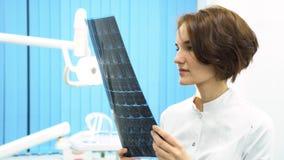 Retrato do close up da mulher intelectual no labcoat branco, olhando a imagem radiográfica do raio X completo do corpo, varredura imagem de stock royalty free