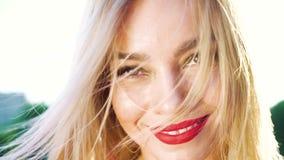 Retrato do close up da mulher loura bonita com batom vermelho na parte externa da luz do sol video estoque