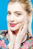 Retrato do close up da mulher loura bonita com o rabo de cavalo e a pele perfeita que vestem a camisa colorida no fundo azul Imagens de Stock