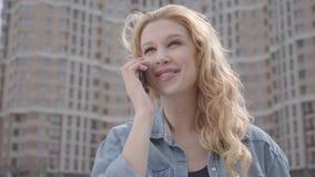 Retrato do close-up da mulher loura segura consideravelmente de sorriso que fala pelo telefone celular na frente do arranha-céus  video estoque