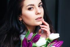 Retrato do close-up da mulher moreno bonita nova com tulipas Imagem de Stock Royalty Free