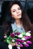 Retrato do close-up da mulher moreno bonita nova com tulipas Imagens de Stock Royalty Free