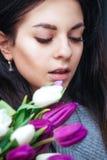 Retrato do close-up da mulher moreno bonita nova com tulipas Imagens de Stock