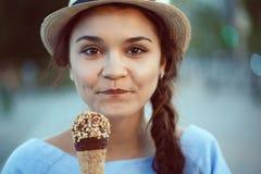 Retrato do close up da mulher moreno caucasiano branca feliz bonita da menina com ondulações em mordentes que come o gelado Fotos de Stock Royalty Free
