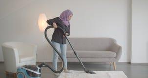 Retrato do close up da mulher muçulmana nova no hijab usando o aspirador de p30 dentro no apartamento vídeos de arquivo