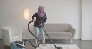Retrato do close up da mulher muçulmana nova no hijab usando o aspirador de p30 e fazendo tarefas domésticas dentro no filme