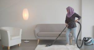 Retrato do close up da mulher muçulmana nova no hijab usando o aspirador de p30 que dança felizmente dentro no apartamento filme