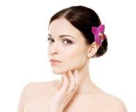 Retrato do close-up da mulher nova, bonita e saudável com uma flor da orquídea imagem de stock