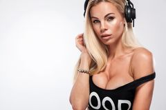 Retrato do close-up da mulher 'sexy' bonita do DJ do louro no fundo branco em fones de ouvido vestindo do estúdio fotografia de stock