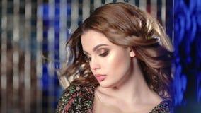 Retrato do close-up da mulher 'sexy' com cabelo de ondulação no estúdio com fundo de néon das luzes azuis vídeos de arquivo
