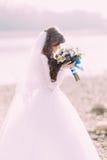 Retrato do close-up da noiva nova no vestido branco e do véu que aspiram o ramalhete do casamento com curva azul fora fotografia de stock royalty free