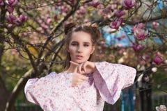Retrato do close up da posição modelo moreno impressionante no jardim de florescência da magnólia fotografia de stock