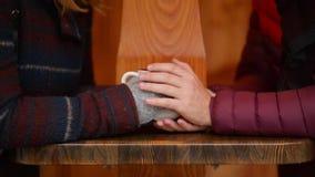 Retrato do close up das mãos de um par que guarda o copo de café sobre uma tabela no inverno que senta-se no café da rua Mulher e video estoque